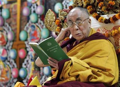 Tibetan spiritual leader Dalai Lama holds a prayer book during at a temple in the northern Indian hill town of Mcleodgunj March 9, 2009. REUTERS/Fayaz Kabli