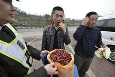 <p>Китайский автолюбитель ест острый перец во время инструктажа со стороны сотрудника службы по обеспечению безопасности дорожного движения в провинции Чунцин 10 марта 2009 года. Полиция на юго-западе Китая решила в буквальном смысле задать перца водителям, чтобы те не заснули за рулем, сообщила в среду газета Chongqing Evening News. REUTERS/Stringer</p>