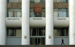 <p>Челове проходит мимо входа в здание парламента Молдавии в Кишиневе 7 марта 2005 года. Правящая в Молдавии Партия коммунистов президента Владимира Воронина стремится удержать власть в стране на выборах в парламент 5 апреля, в которых ей противостоит два десятка конкурентов. REUTERS/Bogdan Cristel</p>