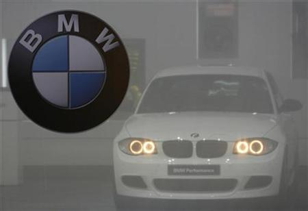 A BMW logo is pictured next to a BMW 116d standing behind a semi-transparent curtain during the first media day of the 79th Geneva Car Show at the Palexpo in Geneva March 3, 2009. REUTERS/Denis Balibouse