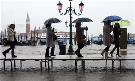 People use a boardwalk to avoid getting wet feet during a period of high water in Venice in this file photo from February 7, 2009.REUTERS/Manuel Silvestri
