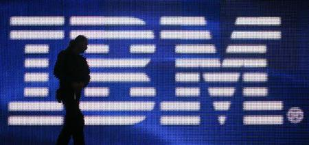 A worker is silhouetted in front of a huge screen with the IBM logo ahead of the CeBIT fair inside a hall in Hanover in this file photo from March 1, 2008. REUTERS/Hannibal Hanschke