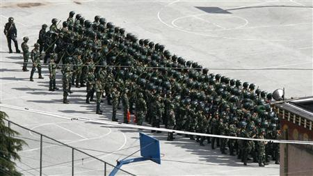 Chinese riot police wearing padding and helmets and holding batons, shields and long sticks, perform drills on basketball courts at a barracks located on the outskirts of Kangding in Sichuan province in this file picture dated February 24, 2009. China warned the West not to ''put its fingers into'' Tibet as the restive region, under heavy security and shut off from the outside world, marked on Saturday the anniversary of last year's deadly riots in Lhasa. REUTERS/David Gray/Files