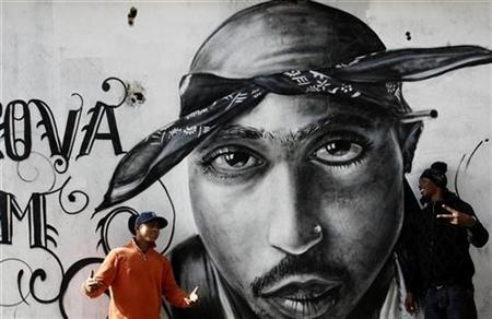 Nuno (L) talks to Sergio Rodrigues ''Sorriso'' next to a graffiti of murdered rapper Tupac Shakur in the Cova da Moura district in Lisbon December 6, 2007. REUTERS/Nacho Doce