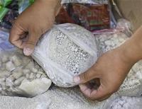 <p>Струдник органов правопорядка Таджикистана демонстрирует пакет с конфискованным героином в Душанбе 30 мая 2008 года. В Таджикистане задержана гражданка Филиппин, которая пыталась вывезти в Стамбул 33 банных халата с героином, спрятанным в 758-ми пуговицах. REUTERS/Shamil Zhumatov</p>