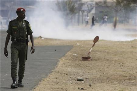 A police watches as demonstrators flee tear gas fired by police during an anti-homosexuality protest outside Dakar's main mosque February 15, 2008. The protest was sparked after the publication, in gossip magazine ''Icone'', of photos of a gay wedding in the mostly Muslim nation where homosexuality is illegal. REUTERS/Normand Blouin