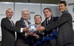 <p>Parties involved in Vancouver Whitecaps FC entering the Major Soccer League pose with a ball during a ceremony in Vancouver, British Columbia March 18, 2009. They are (L to R) - MSL Commissioner Don Garber, BC Premier Gordon Campbell, team executive committee Jeff Mallet, Whitecaps President Bob Lenarduzzi and Mayor Gregor Robertson. The Whitecaps will join the MSL in the 2011 season. REUTERS/Andy Clark</p>