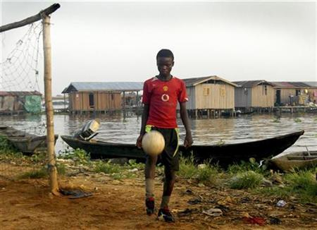 A boy kicks a ball in Iwaya, one of the poorest areas of Lagos, in this undated photograph taken by a child, part of an exhibition in which hundreds of Nigerian kids from the richest and poorest homes in Lagos have documented their lives through pictures. REUTERS/Maxim Zannu/Handout