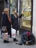 <p>Un mendicante seduto davantio alle vetrine di una gioielleria a Milano. REUTERS/Chris Helgren (ITALY)</p>