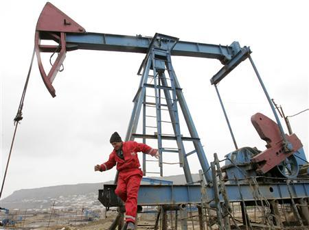 Workers repair an oil pump jack in Baku, March 17, 2009. REUTERS/David Mdzinarishvili