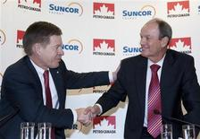 <p>Suncor Chief Executive Rick George (L) and Petro-Canada Chief Executive Ron Brenneman shake hands during a media conference in Calgary March 23, 2009. REUTERS/Mike Sturk</p>