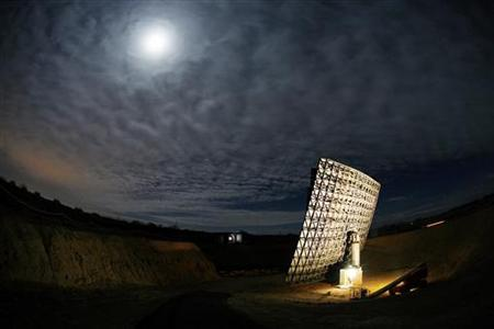 Light from a full moon is reflected off the ''Interstellar Light Collector'' (R) in the Sonoran desert near Three Points November 23, 2007. REUTERS/Jeff Topping