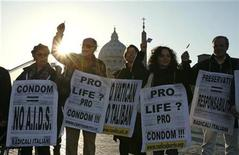 <p>Demonstrators hold placards during a rally to commemorate AIDS victims, staged outside St. Peter's Square at the Vatican March 23, 2009. Demonstrators protested against Pope Benedict XVI's opposition to the use of condoms to stop the spread of AIDS, remarked last week during his trip to Africa. REUTERS/Alessia Pierdomenico</p>