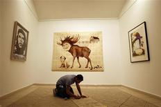 "<p>An artist works underneath paintings which are part of the exhibition ""Chelsea visits Havana,"" in Havana March 24, 2009. The work of more than 30 U.S. artists representing New York City's Chelsea district will be displayed March 28 through May 17. REUTERS/Enrique De La Osa</p>"