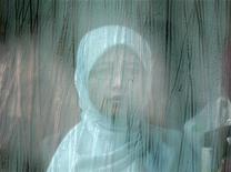 <p>Женщина сидит в автобусе, направляющемся в Куала-Лумпур 14 ноября 2008 года. Мир может погрузиться в экономический мрак, но создатели платья, украшенного 751 бриллиантом, стоимостью в $30 миллионов уверены, что желание выставить напоказ свое богатство никогда не угаснет. REUTERS/Bazuki Muhammad</p>