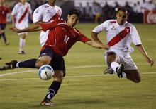 <p>Chileno Fernández e peruano Torres disputam bola em partida das eliminatórias da Copa do Mundo de 2010, em Lima. 29/03/09. REUTERS/Enrique Castro Mendivil</p>