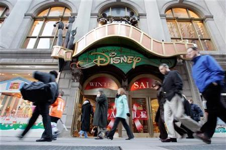 Passers-by walk in front of the World of Disney store in New York January 19, 2006. REUTERS/Keith Bedford
