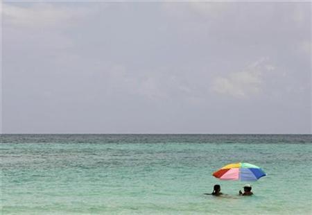 Vacationing Cubans sit in the waters near a beachfront hotel in Varadero, 90 miles (145 km) east of Havana August 5, 2008. REUTERS/Claudia Daut