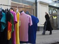 <p>A woman walks past a display of fake designer shirts peddled in front of the Alexander McQueen and Stella McCartney stores in Moscow March 27, 2009. REUTERS/Thomas Peter</p>