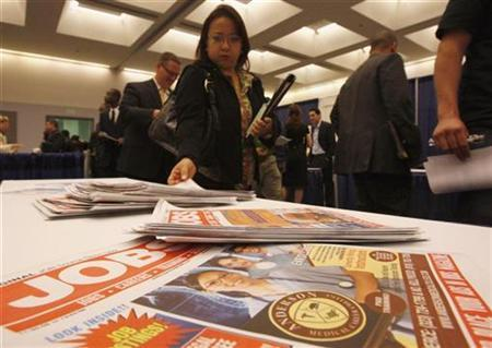 A woman picks up a newspaper advertising jobs at a career fair in Los Angeles February 3, 2009. REUTERS/Lucy Nicholson