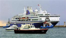 """<p>Круизный лайнер """"Grand Voyager"""" швартуется в порту Кальяри на острове Сардиния 15 февраля 2005 года. Итальянские власти в срочном порядке ищут морской круизный лайнер для размещения участников и гостей саммита """"Большой восьмерки"""", который пройдет в этом году недалеко от острова Сардиния. REUTERS/Stringer</p>"""