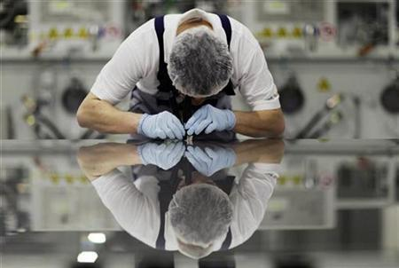 A worker of Signet Solar checks a photovoltaic module in a plant in Mochau near Dresden December 17, 2008. REUTERS/Hannibal Hanschke