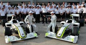<p>Pilotos da Brawn GP, Jenson Button e Rubens Barrichello, posam ao lado dos carros e de membros da equipe no circuito de Sepang, na Malásia 02/04/2009 REUTERS/Shaiful Rizal</p>