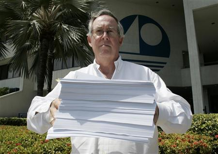 Miami Beach city commissioner Jerry Libbin holds a stack of resolutions from cash-strapped condo associations representing some 135,000 condo owners which he plans to carry to the Florida legislature as he stands outside Miami Beach City Hall in Miami Beach, Florida March 31, 2009. The resolutions from condo associations are pleading with state legislators to change state law to force lenders to pay more toward delinquent monthly association fees when they foreclose on a home. Florida's condominium and homeowners' associations are facing what experts call a trickle-down disaster from the property crisis. Dozens and perhaps hundreds of condo buildings have budget shortfalls as thousands of owners, under water on their mortgages or in foreclosure, stop paying monthly fees. REUTERS/Joe Skipper