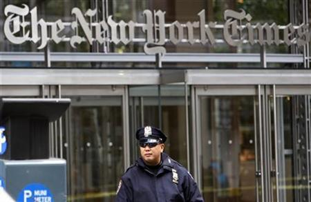 A New York City police officer stands outside the New York Times headquarters building in New York October 22, 2008. REUTERS/Mike Segar