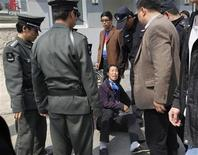 <p>A petitioner sits on the ground as Chinese policemen and security officers try to remove her from the entrance of Peking University in Beijing, April 8, 2009. REUTERS/Reinhard Krause</p>