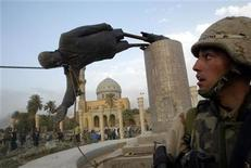 <p>A U.S. soldier watches as a statue of then Iraq President Saddam Hussein falls in central Baghdad April 9, 2003. REUTERS/Goran Tomasevic</p>