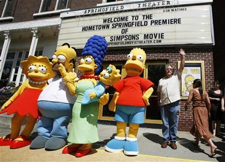 Creator of the show ''The Simpsons'' Matt Groening (R) waves alongside characters (L-R) Lisa, Homer, Marge, Maggie, and Bart Simpson in this file photo from Springfield, Vermont in July, 2007. REUTERS/Lucas Jackson