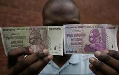 <p>Мужчина демонстрирует купюры достоинством в 200 и 500 миллионов зимбабвийских долларов в Хараре 12 декабря 2008 года. Чтобы исправить экономическую ситуацию в Зимбабве, местные власти вывели зимбабвийский доллар из оборота, сообщили местные газеты в воскресенье. REUTERS/Philimon Bulawayo</p>