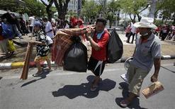 <p>Сторонники экс-премьера Таиланда Таксина Чинавата покидают Дом правительства в Бангкоке 14 апреля 2009 года. Тайские оппозиционеры во вторник сняли осаду с Дома правительства в Бангкоке, решив не идти на конфронтацию с войсками во избежание дальнейших жертв. REUTERS/Sukree Sukplang</p>