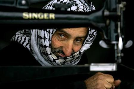 A Palestinian shoemaker looks from behind a sewing machine at his workshop in the Old City of Hebron January 28, 2006. REUTERS/Stoyan Nenov