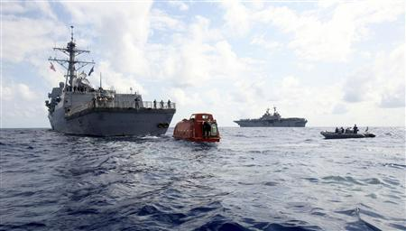 The guided-missile destroyer USS Bainbridge (DDG 96) tows the lifeboat from the Maersk Alabama to the amphibious assault ship USS Boxer (LHD 4) (in background R) to be processed for evidence after the successful rescue of Capt. Richard Phillips in the Indian Ocean off the coast of Somalia in this picture taken April 13, 2009. REUTERS/Megan E. Sindelar/U.S. Navy photo/Handout