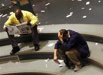 <p>Un trader legge un giornale, mentre un altro simette le mani sulla testa a Wall Street. REUTERS/Joshua Lott (UNITED STATES)</p>