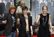 <p>Daniel Radcliffe (C), Rupert Grint (L) and Emma Watson hold their wands before leaving prints in cement at the Chinese theatre in Hollywood, California July 9, 2007. REUTERS/Mario Anzuoni</p>