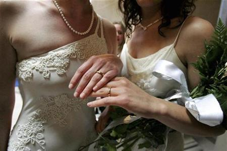 A couple display their wedding rings after exchanging wedding vows at City Hall on the first full day of legal same-sex marriages in San Francisco, California June 17, 2008. REUTERS/Erin Siegal
