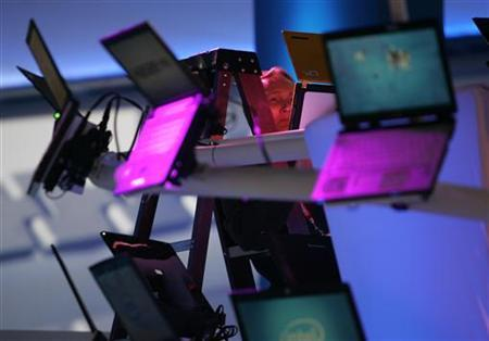 A worker sets up a display of laptop computers at the Intel booth as exhibitors prepare for the Consumer Electronics Show (CES) in Las Vegas, Nevada January 6, 2008. REUTERS/Steve Marcus