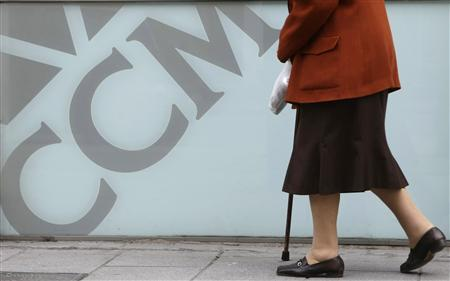 An elderly woman walks past a branch of savings bank Caja Castilla La Mancha (CCM) in central Madrid March 29, 2009. (REUTERS/Sergio Perez)