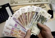 <p>Человек держит в руках рублевые купюры в Санкт-Петербурге 18 декабря 2008 года. Доходы федерального бюджета РФ в текущем году могут оказаться еще на 800 миллиардов рублей, или 2,0 процента ВВП, меньше, чем заложено в уточненном проекте федерального бюджета. Минфин, однако, обещает выполнить все расходные обязательства, взяв недополученные средства из Резервного фонда, но признает, что это серьезно осложнит исполнение бюджета в 2010 году. REUTERS/Alexander Demianchuk</p>
