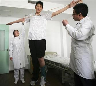 Zhao Liang, who may be the world's tallest person, has his arms measured by doctors before foot surgery at a hospital in Tianjin municipality April 13, 2009. At 2.46 metres (8 ft 1 in) tall, Zhao may well be the world's tallest person. All he needs is to be officially measured. The 27-year-old was recently measured by doctors who were treating him for a foot injury, and was found to be some 10 cm higher than Bao Xishun, the 57-year-old Chinese man currently holding the Guinness World Record for tallest man. Picture taken April 13, 2009. REUTERS/China Daily