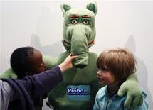 <p>Niños posan con Probo, un robot, en la exhibición del primer prototipo en Bruselas, 21 abr 2009. Un grupo de expertos de Bélgica está desarrollando un amistoso robot para ayudar a calmar la ansiedad en los niños hospitalizados. El robot de peluche Probo, de color verde y con forma de elefante, cuenta con una pantalla táctil en su panza que busca explicar las operaciones a los chicos. REUTERS/Francois Lenoir</p>