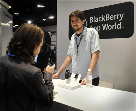 Research in Motion representative Alex Manea (R) guides a convention attendee through a demonstration of the Blackberry App World store on a Blackberry handset at the 2009 CTIA Wireless convention in Las Vegas April 1, 2009. REUTERS/David Becker