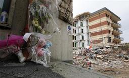 <p>Цветы и игрушки у разрушенного студенческого общежития в Л'Аквилле, Италия 18 апреля 2009 года. Кабинет министров Италии одобрил предложение провести саммит G8, намеченный на 8-10 июля, в город Л'Аквилла, который сильно пострадал от разрушительного землетрясения 6 апреля, сообщил в четверг министр инфраструктуры. REUTERS/Darrin Zammit Lupi</p>