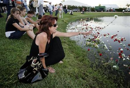 Missy Sullivan (R) of Wellington, FL throws a flower in a pond as patrons attend a memorial service for 21 horses from the Lechuza Caracas team from Venezuela that died mysteriously last week during a match in the U.S. Open at the International Polo Club Palm Beach, in Wellington, Florida April 23, 2009. REUTERS/Joe Skipper