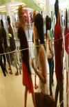 <p>Shoppers are reflected in a mirror as they walk at a shopping centre in Singapore March 14, 2007. REUTERS/Vivek Prakash</p>