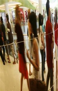 Shoppers are reflected in a mirror as they walk at a shopping centre in Singapore March 14, 2007. REUTERS/Vivek Prakash