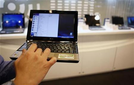 An employee poses with the low-cost Asus Eee PC laptop inside a mall in Taipei February 25, 2009. REUTERS/Nicky Loh